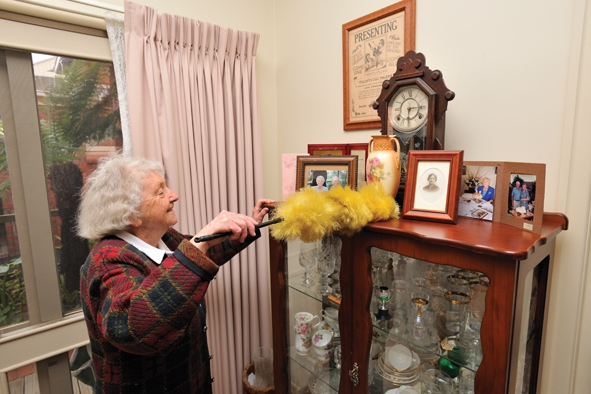 Senior lady dusting crystal cabinet